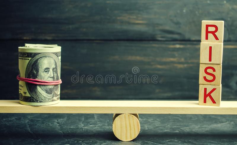 Dollars and the inscription risk are on the scales. The concept of financial and economic risk. Unreliable investment. Unpaid loan stock images