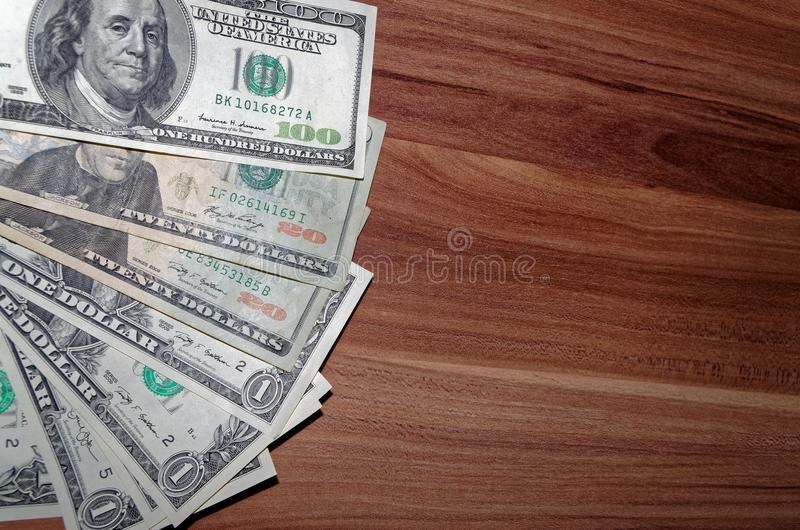 Dollars lying out on the wooden background. American dollars laid out on the right side of the wooden background royalty free stock photos