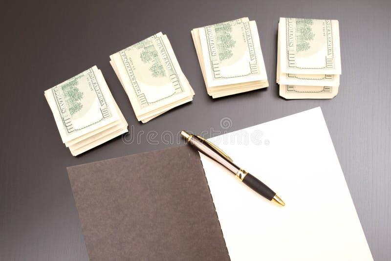 Dollars met een voorbeeldenboek stock foto's