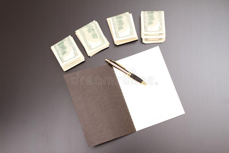 Dollars met een voorbeeldenboek stock afbeeldingen