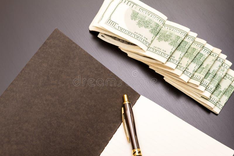 Dollars met een voorbeeldenboek stock fotografie