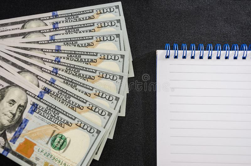 Dollars and notebook on a black background. Close-up. Place for text. stock image