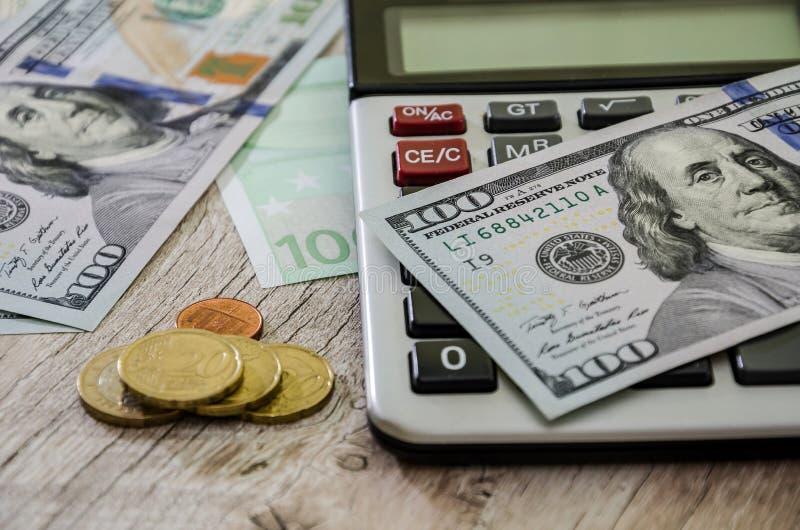 Dollars, pièces de monnaie et calculatrice sur la table, plan rapproché image libre de droits