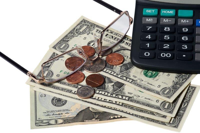 Dollars, pièces de monnaie, verres et calculatrice placés sur une table image stock