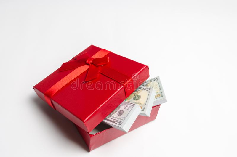 Dollars in a red gift box on a white background. Search for a gift for the holiday. Gift Certificate. The best gift is money. Cost royalty free stock photos