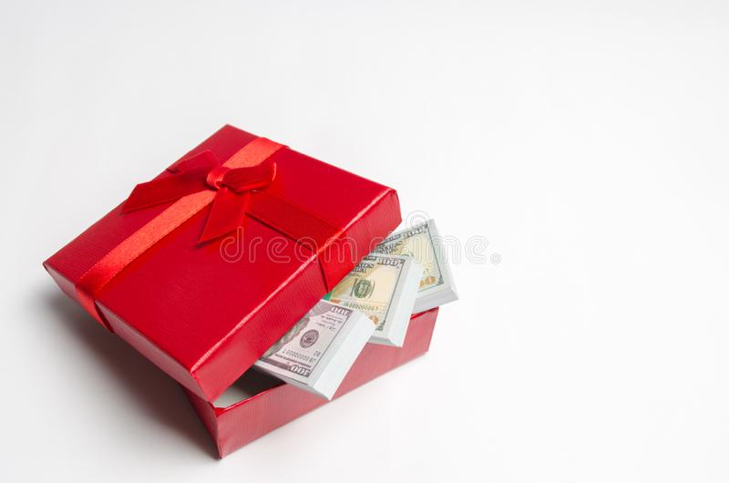 Dollars in a red gift box on a white background. Search for a gift for the holiday. Gift Certificate. The best gift is money. Cost royalty free stock images