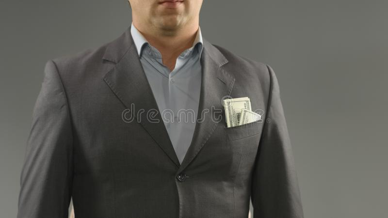 Dollars in rich male suit pocket, money saving, income or bribery concept. Stock photo royalty free stock photography