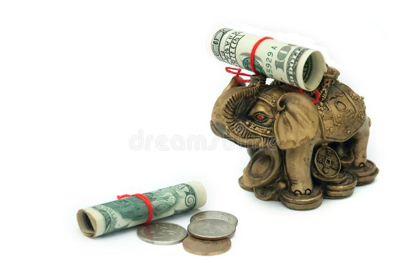 Dollars rolled up in a tube and tied with a red thread and coins and a golden elephant on a white background. Feng Shui. royalty free stock image