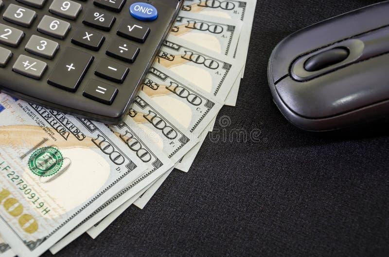 Dollars, souris d'ordinateur et calculatrice sur un fond noir Plan rapproch? Place pour le texte photographie stock