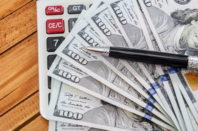 Dollars US, calculatrice et stylo photographie stock libre de droits