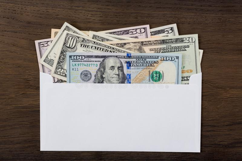 Dollars in white envelop on wooden background. stock images