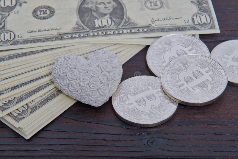 Dollarsedlar, bitcoins och hjärta på en tabell royaltyfri foto