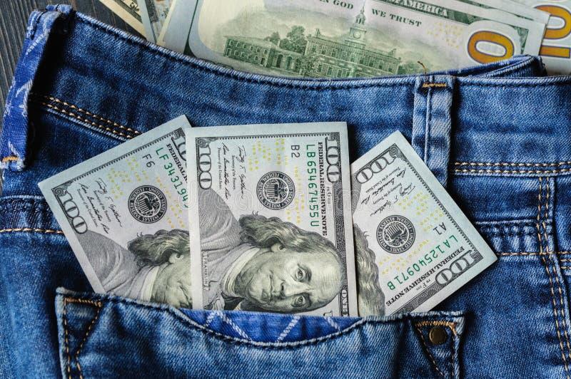 Dollarsedlar i bakfickan av jeans Förtjänster kontant fotografering för bildbyråer
