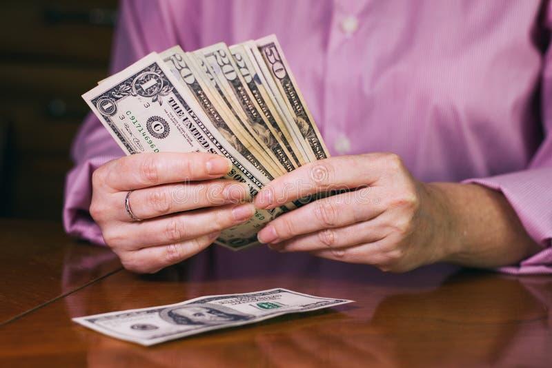 Dollarsedlar i kvinnliga händer royaltyfri fotografi