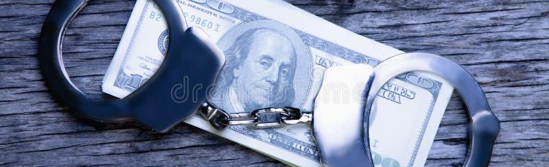 Dollarsedlar och handbojor som symbol av finansiella brott arkivfoto