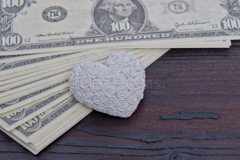 Dollarsedlar och hjärta på en trätabell arkivfoton