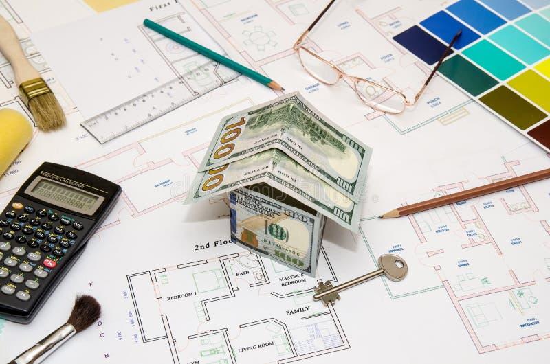 Dollarsedlar som modellhus på ett konstruktionsplan royaltyfri foto