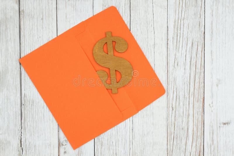 Dollarzeichensymbol mit orange Umschlag auf strukturiertem verwittertem Tüncheholzhintergrund stockfotografie