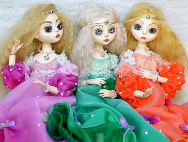 Dolls in beautiful dresses. On a light background royalty free stock photo