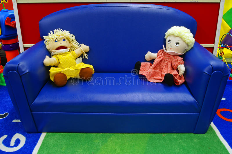 Dolls on the couch at daycare. Dolls sit on the couch in a daycare setting done in bright primary colors stock image