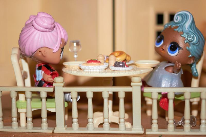 Dolls at tables for meal at doll house stock images