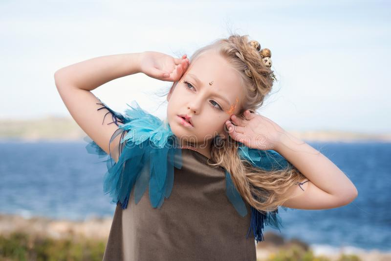 Pretty girl in a fairy makeup stretches after a nap on the beach royalty free stock images