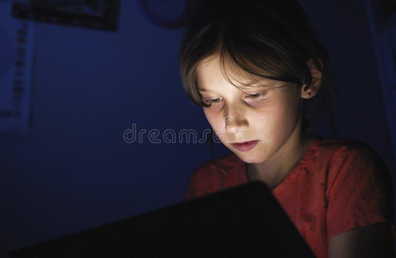 Dolly geschoten Kaukasisch meisje in bed het spelen tablet in Internet in donkerblauw licht onder blacket stock fotografie