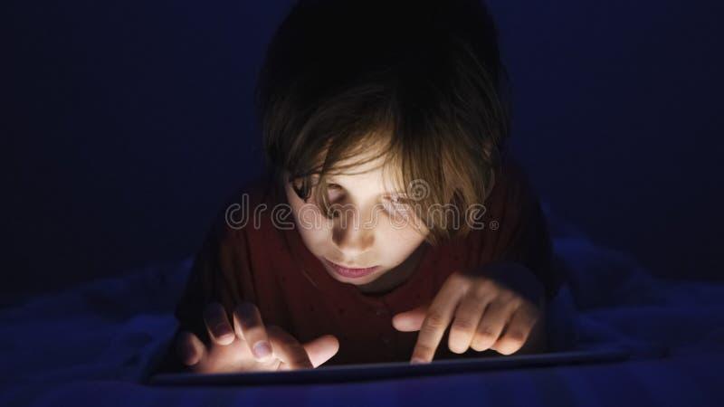 Dolly geschoten Kaukasisch meisje liggend in bed het spelen tablet in Internet in donker licht onder blacket stock afbeelding