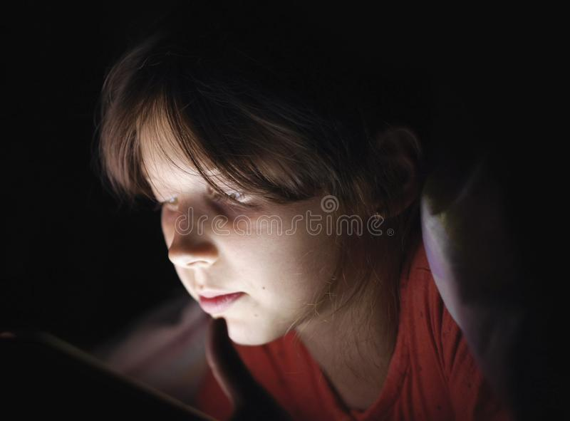 Dolly geschoten Kaukasisch meisje liggend in bed het spelen tablet in Internet in donker licht onder blacket royalty-vrije stock afbeelding