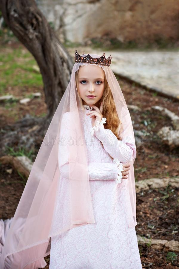 Dolly princess of the fairy elves stands in a magical enchanted forest and enchantingly looks stock photography
