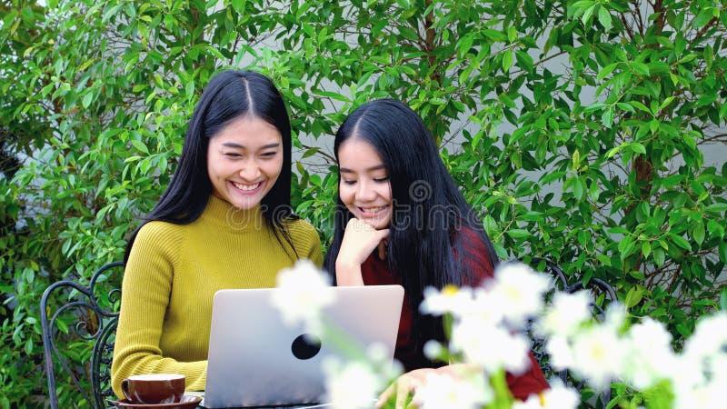 Dolly schot van Leuke Aziatische tiener met laptop computer bij tuin stock afbeeldingen