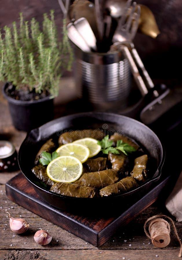 Dolma, folhas de uva enchida com arroz e carne triturou a carne em uma frigideira do ferro fundido em um fundo de madeira velho C fotografia de stock