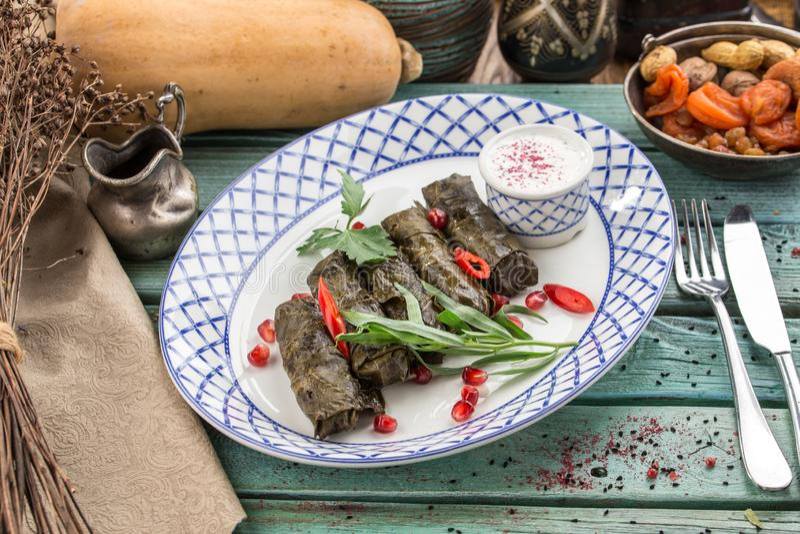 Dolma stoppade druvasidor med ris och kött på den blåa trätabellen fotografering för bildbyråer