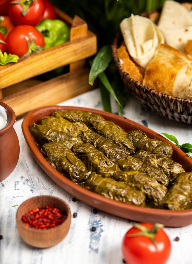 Dolma tolma, sarma - stuffed grape leaves. With rice and meat. On kitchen table with yogurt, bread, vegetables. Traditional Caucasian, Ottoman, Turkish and royalty free stock photos