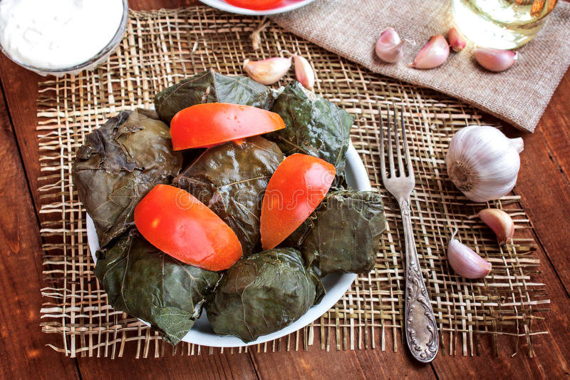Dolma, tomatoes and garlic on a table royalty free stock photo