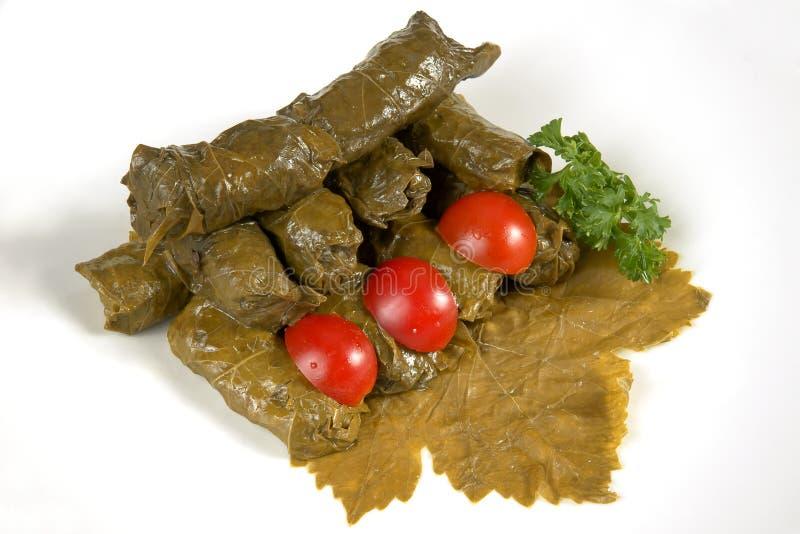 Dolmas (sarma, dolmadakia) on grape leaf. Dolmas (sarma, dolmadakia) stuffed with rice on grape leaf with tomato and parsley royalty free stock images