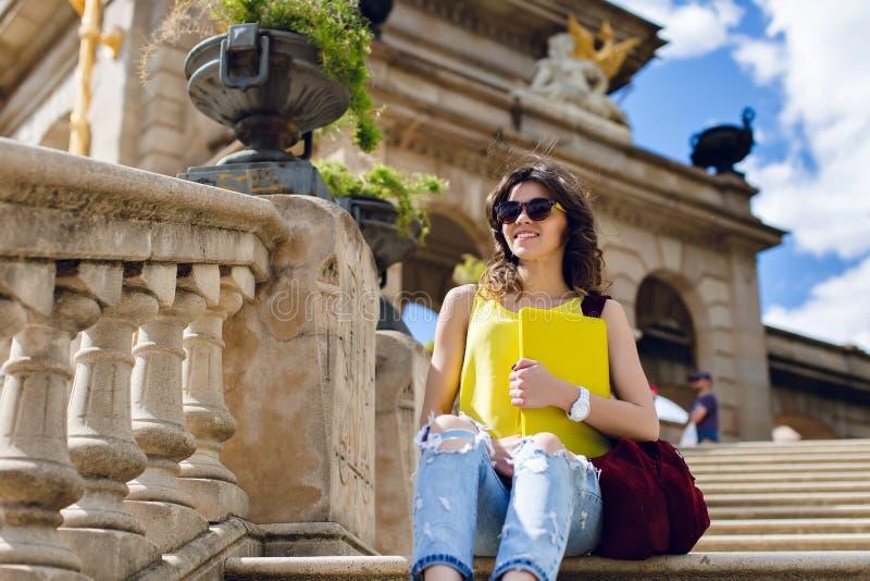 Dolnego widoku brunetki ładna dziewczyna siedzi na betonowych schodkach na starym architektury tle w okularach przeciwsłonecznych zdjęcia royalty free