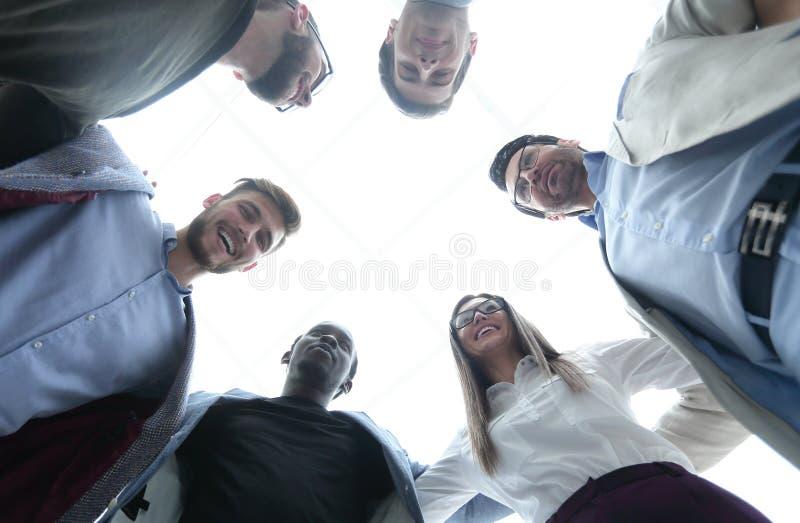 Dolny widok biznesowi drużyna stojaki wpólnie, tworzący okrąg zdjęcia stock