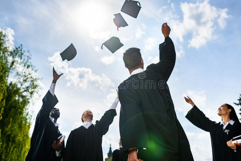 dolny widok potomstwa kończył studia uczni rzuca w górę kapeluszy przed zdjęcie stock