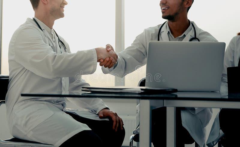Dolny widok u?cisk d?oni medyczni koledzy przy spotkaniem w biurze zdjęcie royalty free