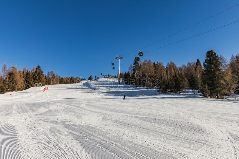 Dolomia, area dello sci con i bei pendii e cielo blu Pendio vuoto dello sci nell'inverno un giorno soleggiato Prepari il pendio d fotografia stock libera da diritti