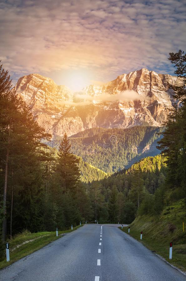 Dolomite Alps in Italy. Beautiful day. The road passes in the co stock photography