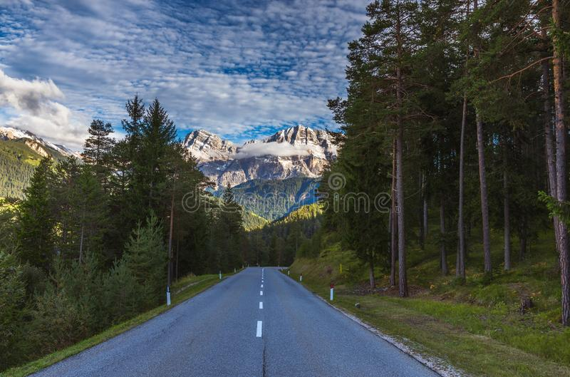 Dolomite Alps in Italy. Beautiful day. The road passes in the coniferous forests at the foot of limestone and dolomite rocks. The stock photos
