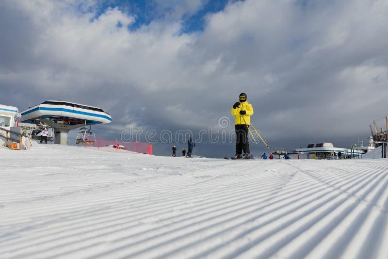 Dolomites, área do esqui com inclinações bonitas Um esquiador em um revestimento amarelo na inclinação do esqui fotografia de stock