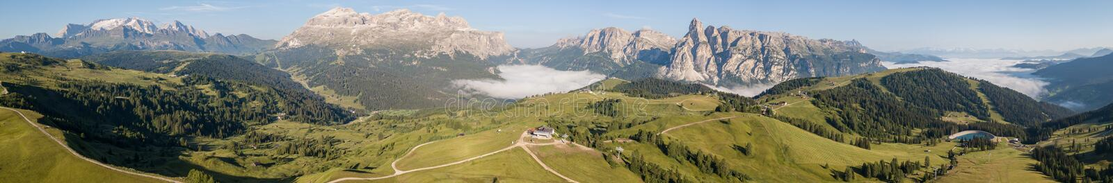 Dolomites, Italy. Amazing drone aerial landscape at Sella, Gardenaccia and Marmolada massifs. Fog at the bottom of the valley royalty free stock images