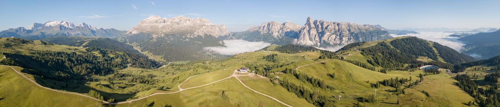 Dolomites, Italy. Amazing drone aerial landscape at Sella, Gardenaccia and Marmolada massifs. Fog at the bottom of the valley stock photo