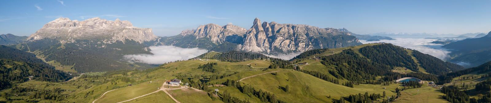 Dolomites, Italy. Amazing drone aerial landscape at Sella and Gardenaccia massifs. Fog at the bottom of the valley stock photography