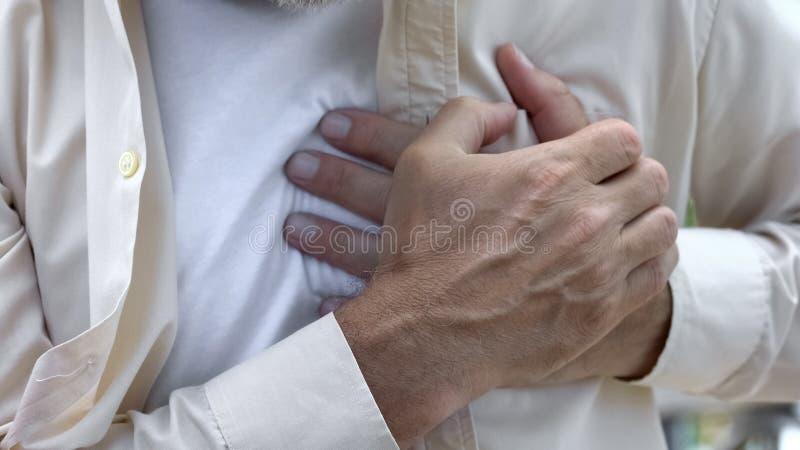 Dolor agudo de la sensación adulta del hombre, tocando el pecho, riesgo de ataque del corazón, cardiología fotos de archivo libres de regalías