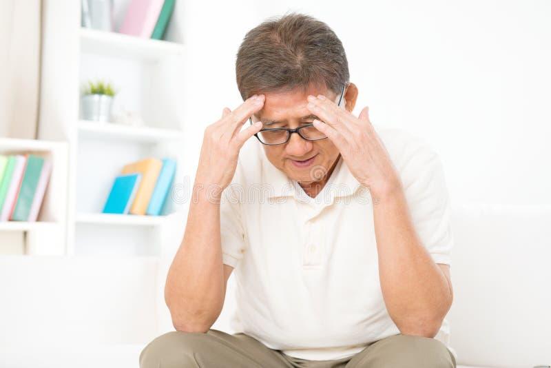 Dolor de cabeza asiático maduro del hombre imagen de archivo libre de regalías