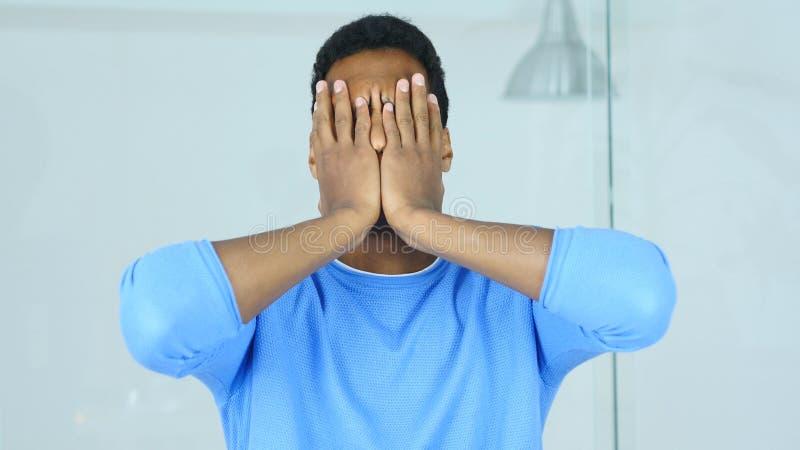 Dolor de cabeza, cara afroamericana de la cubierta del hombre del trastorno con las manos fotografía de archivo